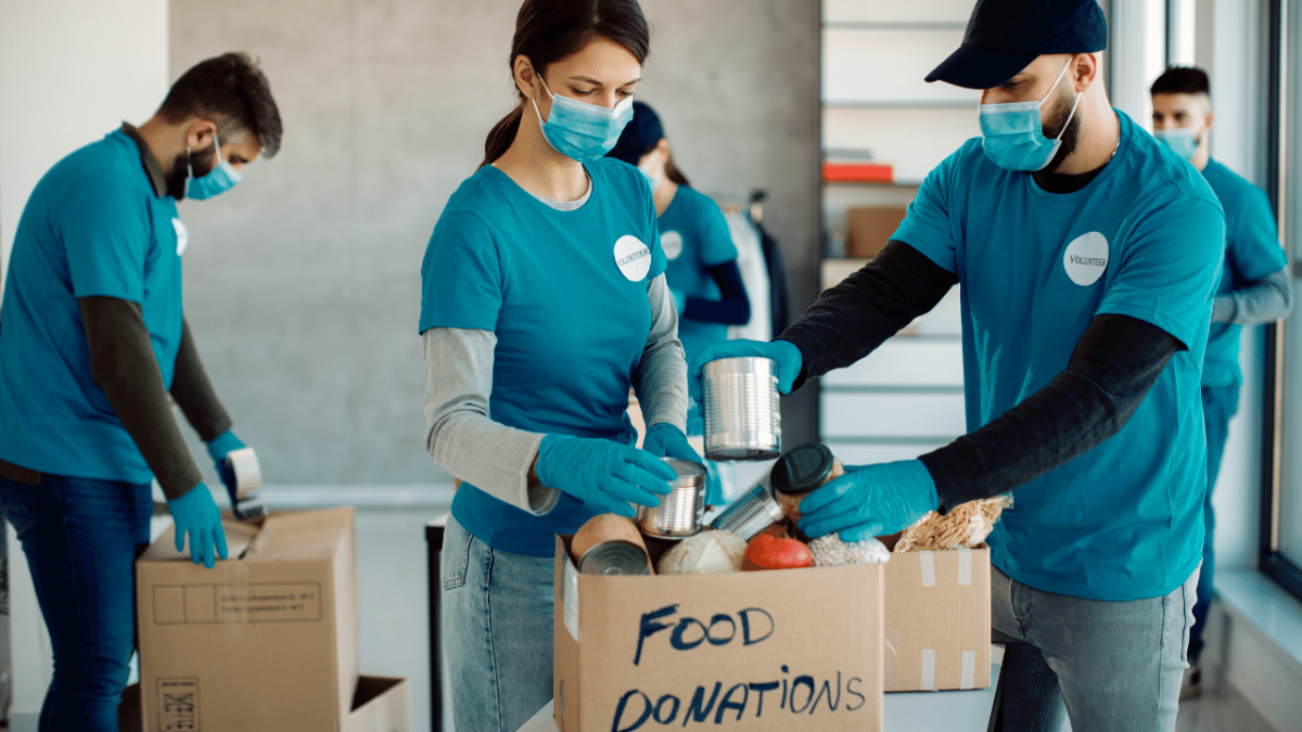Volunteers in blue shirts and blue face masks sorting food donations
